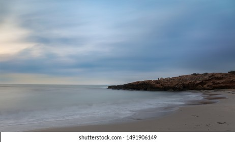 Half an hour before sunrise. A beautiful bay for swimming with a sandy beach in the early morning before sunrise near the Spanish town of Torrevieja. Soft waves through long exposure.