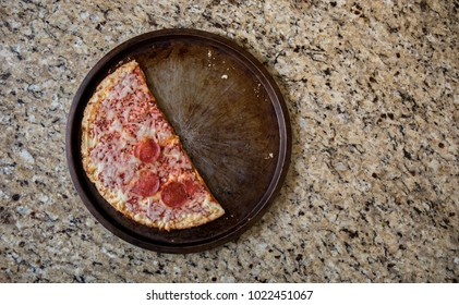 Half of a leftover frozen pizza discarded on the counter top.