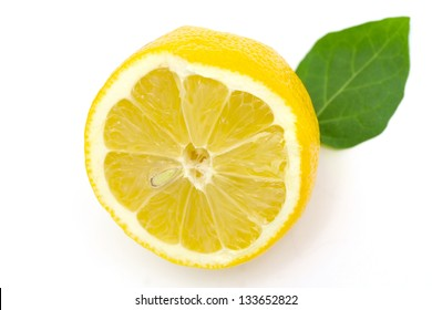 half a lemon with a green leaf on white background