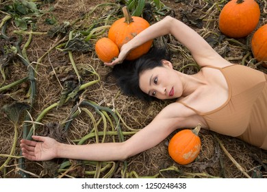 Half length adult woman dancer dressed in earth tones, lying stretched out in a farm field holding a pumpkin, in Ellington, Connecticut.