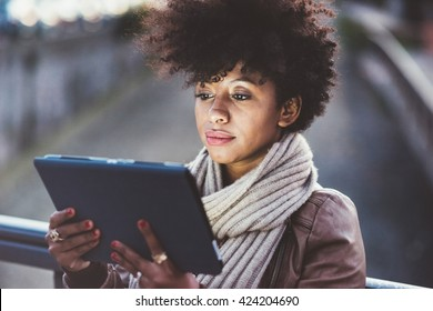 Half length of beautiful black curly hair african woman using tablet in town by night, face illuminated by screen light - technology, communication, social network concept