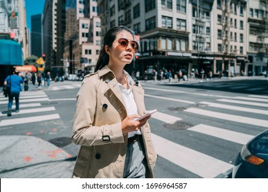 half length of beautiful young woman walking outside and reading text message on mobile phone. confident lady wearing stylish sunglasses and holding cellphone in city street on spring sunny day