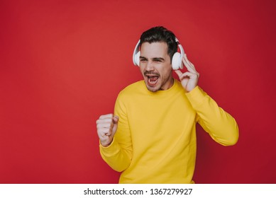 Half length of dark-haired unshaven man wearing headphones and singing loudly a song. He is in yellow sweater and looking away on red background. Human emotions and face expressions concept. Copy