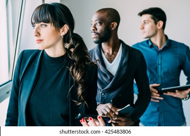 Half length of multiracial business people working posing indoor, holding technological devices, overlooking serious - seriousness, business, determination concept - focus on the woman