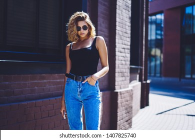 Half length portrait of arrogant female caucasian model dressed in denim jeans posing on publicity area, confident hipster girl 20s in fashionable sunglasses looking at camera on urban setting