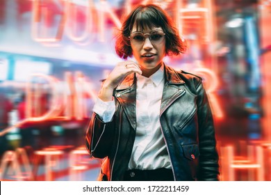 Half length portrait of attractive Caucasian party girl posing near neon wall during night walk in New York, beautiful female tourist in trendy streetwear and stylish spectacles for vision correction