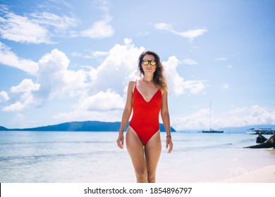 Half length portrait of attractive Caucasian swimmer looking at camera during leisure day at tropical beach of Seychelles, beautiful girl in sunglasses posing at seascape Bahamas horizon