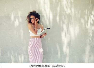 Half length portrait of attractive curly hair female standing with touch pad against copy space area holding touch pad. Well dressed woman using networking connection to internet on her digital tablet