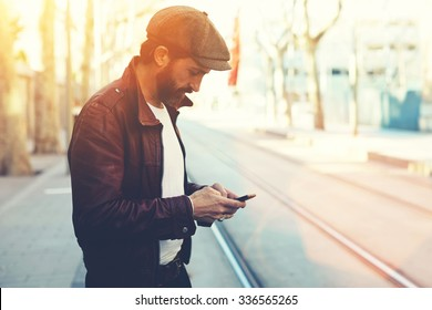 Half length portrait of bearded male with retro style using cell telephone while standing in urban setting, man dressed in stylish clothes chatting on smart phone during walking in cool spring day