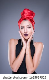 Half length portrait of a beautiful caucasian woman wearing a black top and red turban. Fashion portraiture. Isolated on grey background. Portrait orientation.