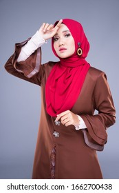 Half length portrait of a beautiful female model wearing a modern kebaya dress and hijab, a lifestyle apparel for Muslim women isolated on grey background. Beauty and hijab fashion concept.