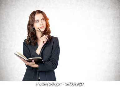 Half length portrait of beautiful young businesswoman or student with long wavy hair holding pencil and notebook and thinking while looking sideways. Concrete wall background. Mock up