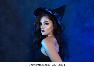 half length portrait of beautiful young woman in witch dress posing next to color background
