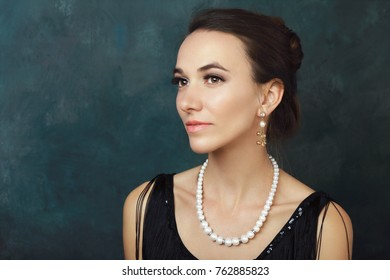 half length portrait of beautiful young elegant woman with pearls in black dress posing next to color background