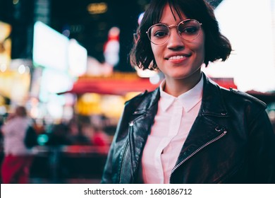Half length portrait of carefree hipster girl in spectacles smiling at camera during evening sightseeing for visiting nigth Manhattan in New York, pretty woman in fashionable leather jacket posing