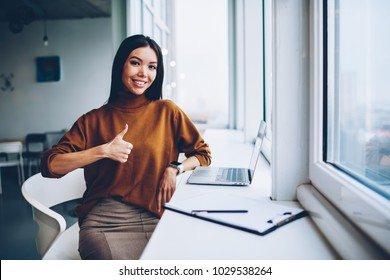 Half length portrait of cheerful asian office manager satisfied with career in company sitting at working place showing finger up, prosperous business woman with ok sign enjoying quality of laptop