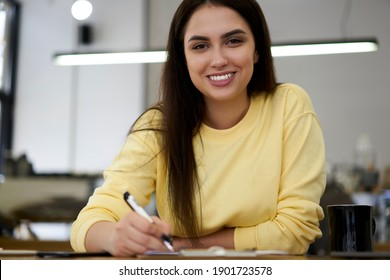 Half length portrait of cheerful brunette woman writer enjoying working on freelance in coffee shop making notes, cheerful caucasian hipster girl student holding pen looking at camera while learning
