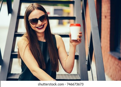 Half length portrait of cheerful brunette woman in stylish sunglasses having fun during strolling at street with coffee cup.Happy cute hipster girl looking at camera while sitting at urban setting