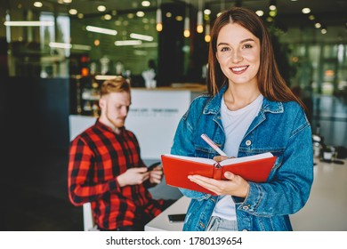 Half length portrait of cheerful Caucasian student making journalistic project using pen and education copybook, successful female person with knowledge textbook in hands smiling at camera