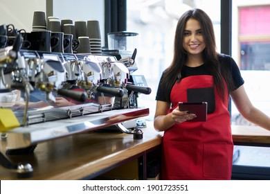 Half length portrait of cheerful caucasian woman barista using digital tablet app for checking orders online, smiling experiencer girl waitress using gadget for organizing job process in coffee house