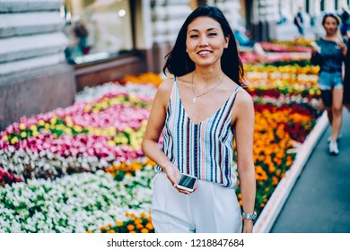 Half length portrait of cheerful female traveler sending messages via mobile strolling on street,happy asian girl enjoying leisure outdoors checking mail on phone waiting for feedback from friend