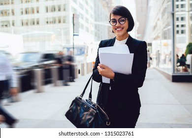 Half length portrait of cheerful female economist standing in Manhattan downtown street with paper documents and smiling at camera, happy successful woman in suit feeling good ready for interview