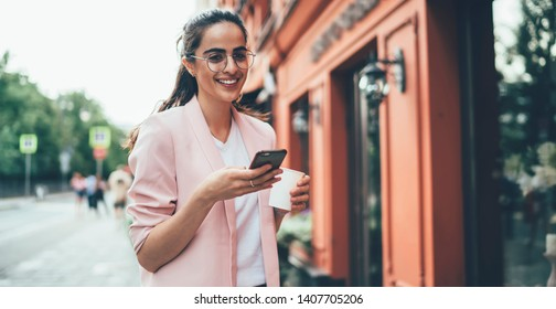 Half length portrait of cheerful Georgian woman in optical eyewear smiling at camer during coffee time in new city for exploring, international positive female tourist in spectacles holding cellphone