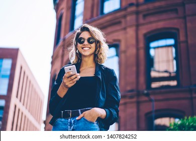 Half length portrait of cheerful hipster girl looking at camera while using smartphone for creating travel publication, smiling woman in sunglasses enjoying spring day and good internet connection