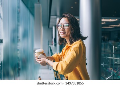 Half length portrait of cheerful hipster girl in classic glasses smiling at camera during free time at public place, positive Chinese female blogger holding smartphone device for surfing internet