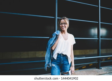 Half length portrait of cheerful hipster girl in optical eyewear for vision correction looking at camera during leisure time on publicity area, happy female teenager in denim apparel outdoors