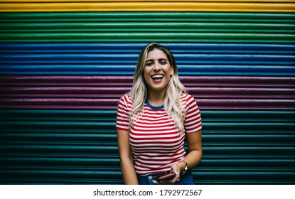Half length portrait of cheerful Spanish hipster girl laughing at camera during smartphone blogging at colorful copy space, grinning female millennial satisfied with leisure pastime at publicity area