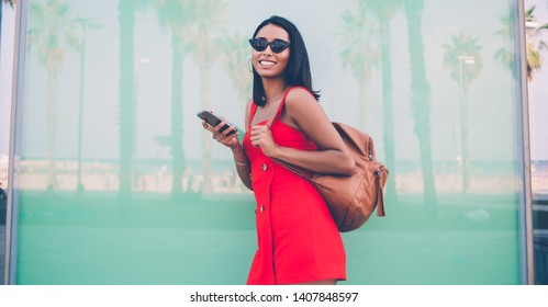 Half length portrait of cheerful woman in fashionable sunglasses holding mobile phone for chatting in hands and laughing at camera during day for walking, gladden jubilate hipster girl phoning