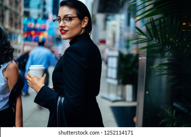 Half length portrait of confident female financial manager turning around on modern street in business district, successful woman professional with coffee to go looking at camera in New York