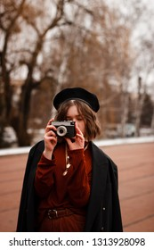 Half length portrait of curly girl photografer taking picture in red sweater and black hat. Street photo