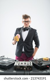 Half length portrait of DJ holding cup with donut, placed donut on turntable, stylish look in tuxedo with hands stretched isolated on white, concept of food at work