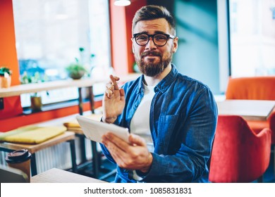 Half length portrait of excited hipster man hoping for luck in internet contest holding digital tablet and waiting on winning results.Emotional blogger with crossing fingers expecting on success
