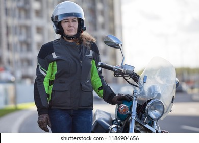 Half length portrait of female motorbiker in safety outfit standing near classic bike on urban street