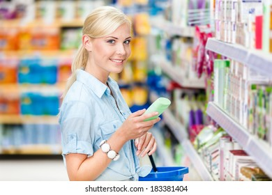 Half length portrait of girl at the shop choosing cosmetics among the great variety of products. Concept of consumerism, retail and purchase