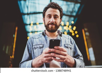 Half length portrait of handsome caucasian bearded guy holding mobile phone connected to 4G for blogging, casually dressed male hipster using modern smartphone outdoors satisfied with updates