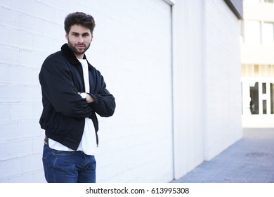 Half length portrait of handsome caucasian model dressed in casual clothing standing near copy space area for your advertising text message and looking on camera. Bearded hipster in trendy spring wear