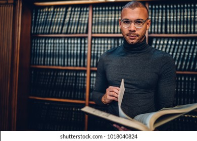 Half length portrait of handsome male writer standing with book on promotional background in library doing research,serious scientist spending time on autodidact learning information from encyclopedia