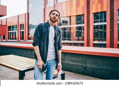 Half length portrait of handsome man in jeans apparel standing on urban setting background, serious  caucasian hipster guy looking at camera dressed n trendy casual street style wear and spectacles