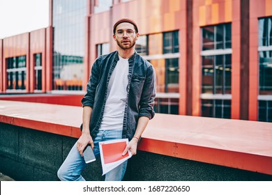 Half length portrait of handsome trendy dressed male designer in eyewear posing on urban setting background with documents, 20s confident skilled caucasian man student standing in college campus
