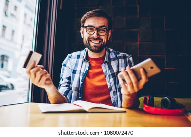 Half length portrait of happy bearded young man dressed in casual outfit smiling at camera while holding credit card and making money transaction via 4G internet connection on smartphone device