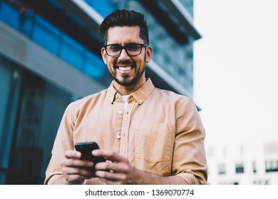 Half length portrait of happy emotional man in spectacles for vision correction looking at camera and laughing during time for using modern technology, concept of communication and digitalisation