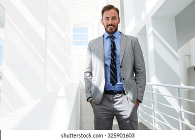 Half length portrait of a happy smiling successful men manager posing while standing on the corridor of office building, cheerful smart businessman dressed in elegant suit resting after conference
