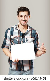 half length portrait of happy young man holding blank leaf standing next to color background in photostudio