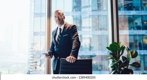 Half length portrait of intelligent male corporate manager formally dressed holding cellular phone for banking and looking at camera during working time in office, business man in spectacles