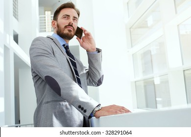 Half length portrait of a intelligent man lawyer calling with cell telephone while standing in modern office space, young confident male entrepreneur speaking on smart phone while rest after meeting