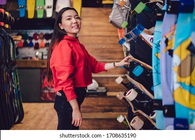 Half length portrait of Japanese hipster girl in trendy clothing posing near rack in store spending time for choosing skateboard from shop assortment, millennial Asian teenager buying longboard